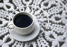 Cup of coffee on wrought iron garden table Royalty Free Stock Photos