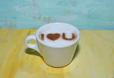 Cup of coffee with on yellow and blue board. Cappuccino mug with cinnamon heart  on yellow blue  board , with i love you sign Stock Photos