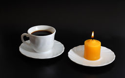 Cup of coffee and yellow candle. Black background Stock Photo