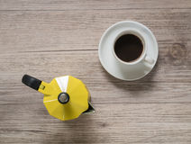 Cup of coffee and Yellow coffee maker kettle on wooden table Stock Photography