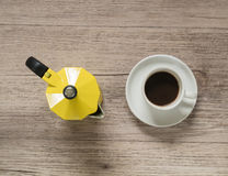 Cup of coffee and Yellow coffee maker kettle on wooden table Stock Photos