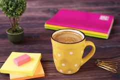A cup of coffee. Yellow cup of white dots. Around office desk supplies in bright, neon colors - notebooks, gold pins, stickers. And plant bonsai and polka dot stock photos
