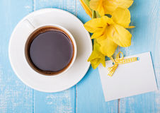Cup of coffee, yellow flowers and blank paper card on blue woode Stock Photos