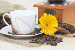 Cup of coffee, yellow gerbera and coffee beans Stock Photos