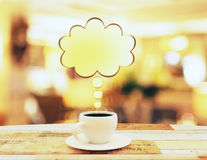 Cup of coffee with yellow speach bubble on wooden table Royalty Free Stock Photo