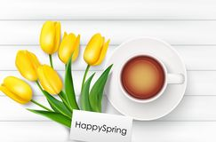 Cup of coffee with yellow tulips and paper on a white wooden background Royalty Free Stock Image