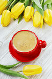 Cup of coffee with yellow tulips Stock Images