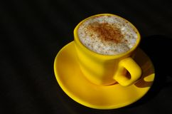 Cup of coffee. Yellow cup of coffee with whipped cream on black background Stock Image