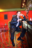 Cup of coffee and young man. Cup of coffee, young thoughful man and bar table in red interior Royalty Free Stock Photo