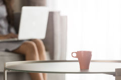 A cup of coffee with Young woman using laptop at home, selective Stock Image