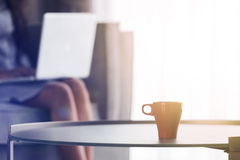 A cup of coffee with Young woman using laptop at home Royalty Free Stock Photo