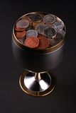 Cup of coins. Silver cup of plenty Stock Photography