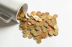 Cup of coins spilling out. Isolate on white background Stock Photos