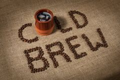A cup of cold brewed coffee. With coffee beans on burlap background royalty free stock photo