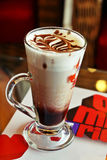 A cup of cold coffee, designed with choco sauce. On a coffee table Royalty Free Stock Photos