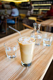A cup of cold ice coffee with milk and tube to drink in a glass on wooden background with carafe of water. Royalty Free Stock Photography