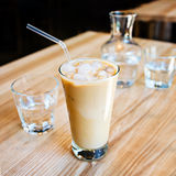 A cup of cold ice coffee with milk and tube to drink in a glass on wooden background with carafe of water. A cup of cold ice coffee frappe with milk and tube to Stock Images