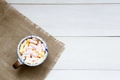 Cup of colorful marshmallows on the wooden table, top view royalty free stock photography