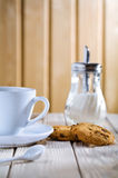 Cup with cookies and sugar dispenser on table Royalty Free Stock Photos