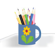 Cup with crayons. Mug with flower with colorful crayons on the table Stock Image
