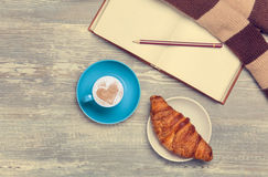 Cup, croissant and book Stock Images