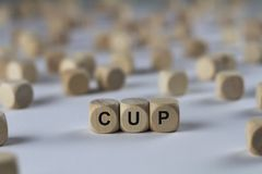 Cup - cube with letters, sign with wooden cubes. Cup - wooden cubes with the inscription `cube with letters, sign with wooden cubes`. This image belongs to the stock photo