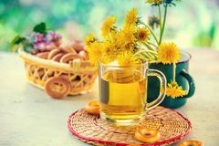 A cup of herbal tea. A cup of dandelion herbal tea on a wooden ta Stock Photography