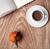 Cup of dark coffee, mandarin, opened book Stock Images