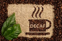 Cup with decaf text written. As aroma of no-caffeine hot beverage inside scattered coffee beans frame on brown burlap bag background stock images
