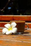 A cup of delicious coffee with plumeria. Royalty Free Stock Photography