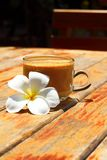 A cup of delicious coffee with plumeria. Stock Photo