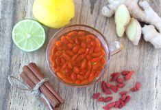 Cup of delicious dietary Goji berries tea. Cup of delicious dietary Goji berry tea on wooden desk with lime, lemon, ginger and cinnamon Stock Image
