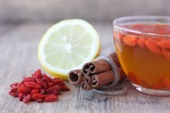 Cup of delicious dietary Goji berries tea. Cup of delicious dietary Goji berry tea on wooden desk with lime, lemon, ginger and cinnamon Stock Images