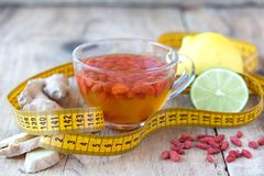 Cup of delicious dietary Goji berries tea. Cup of delicious dietary Goji berry tea on wooden desk with lime, lemon, ginger and yellow sartorial meter Royalty Free Stock Image