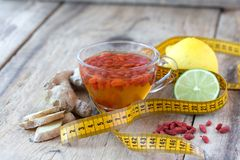 Cup of delicious dietary Goji berries tea. Cup of delicious dietary Goji berry tea on wooden desk with lime, lemon, ginger and yellow sartorial meter Royalty Free Stock Photo