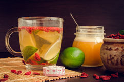 Cup of delicious dietary Goji berry tea. With lime and honey on wooden background with measuring tape. Wolfberry for a healthy diet. Alternative medicine Stock Photography