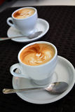 Cup of delicious foamy cappuccino on the black background Stock Photos