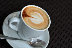 Cup of delicious foamy cappuccino on the black background Royalty Free Stock Photos