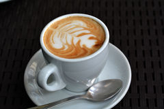 Cup of delicious foamy cappuccino on the black background Royalty Free Stock Photography