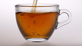 Cup of delicious fragrant black tea for breakfast. Slow motion. Cup of delicious fragrant black tea for breakfast, in a transparent glass cup is poured black tea stock footage
