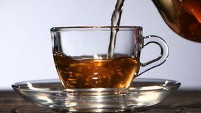 Cup of delicious fragrant black tea for breakfast. Slow motion. Cup of delicious fragrant black tea for breakfast, in a transparent glass cup is poured from stock footage