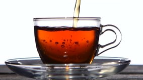 Cup of delicious fragrant black tea for breakfast. White background. Cup of delicious fragrant black tea for breakfast, in a transparent glass cup is poured from stock video footage