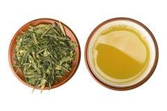 Cup des grünen Tees mit Blättern Stockfotos