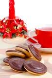 Cup des roten Tees, der Schokoladenplätzchen und der Kerze stockfoto