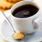 Cup des schwarzen Kaffees und des Löffels mit braunem Zucker Stockbild
