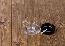 Cup with dish and cigarette in black ashtray Stock Photography