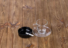 Cup with dish and cigarette in black ashtray Royalty Free Stock Image