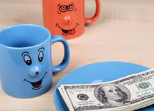 Cup and dollar. The cup is looking for dollars. Two Cup and dollar. The cups is looking for dollars on the plate Stock Photo
