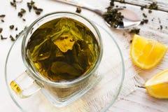Cup of dreen tea with lemon on a table Stock Photos