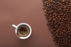 Cup of drunk coffee on brown background with beans Royalty Free Stock Photos